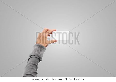 Pullover hand in sweater jacket hold business card mock up in arm. Hands with sleeve slip-on holding paper identity mockup presentation in fingers. Isolated on gray background. Card document holder.