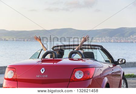 NESSEBAR, BULGARIA - APRIL 30: Woman in the car Renault Megane Coupe Cabrio on the waterfront on April 30, 2016 in Nessebar, Bulgaria.