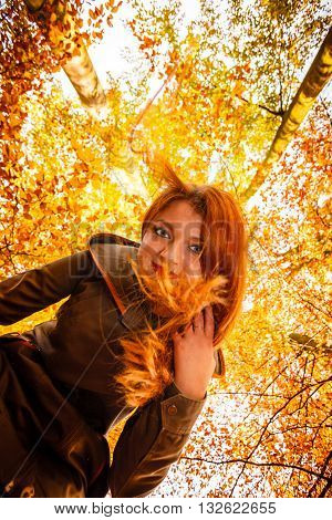 Season and happy people concept. Unusual low angle view of young happy woman in autumn park. Beauty redhaired girl relaxing walking outdoor