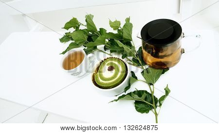 Cake tea matcha green tea for print or promote Prob have Mulberry leaf in my plant and green tea in pot ceramic cup background is wood chair white color.