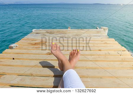Womans Legs On A Dock While Relaxing On Seaside