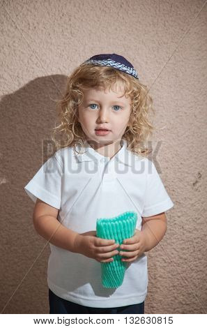Adorable little boy with long blond curls and blue eyes in the Jewish knitted skullcap. He holds the case for the holiday citrus. Autumn holiday of Sukkot
