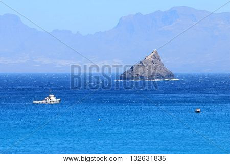 Tug and boat near the cliff with a lighthouse