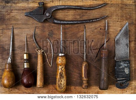 Leather craft tools on a wooden background. Craftmans work desk. Piece of hide and working handmade tools on a work table. Top view.