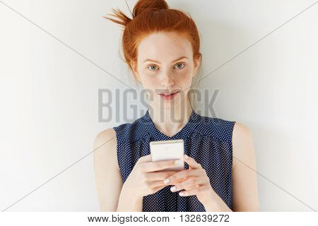 Beautiful Young Businesswoman In Spotted Dress, Reading News Or Checking Email On Cell Phone. Redhea
