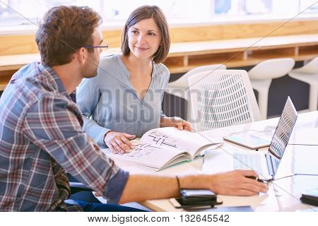 Adult female tutor smiles politely at the male student that she is mentoring to help him reach his full potential