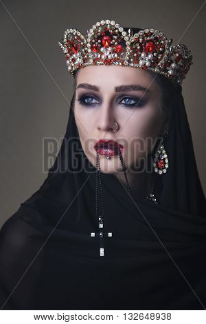 Black queen in a crown and with a crucifix in lips