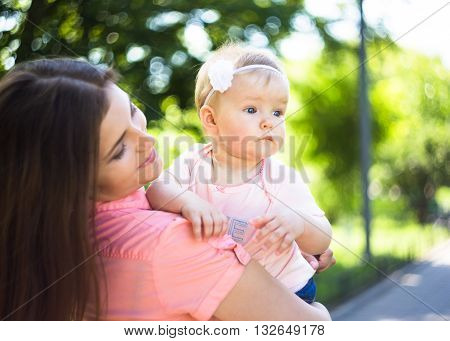 Youmg happy woman playing with her cute baby in summer sunny park outdoor. Mothercare picture.