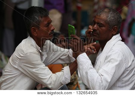 Pune India - ‎July 11 ‎2015:A streetside barber shaves a pilgrim during a huge pilgrimmage in India