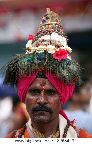 Pune India - July 11 2015: A portrait of a Vasudev pilgrims who are devotees of Lord Vishnu and wear a conical hat with peacock feathers. Vasudev has been a traditional since many years in Maharashtra. THese pilgrims go around singing praises of Lord Vish