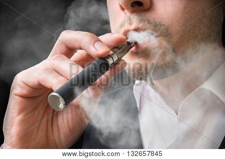 Man is smoking electronic cigarette or vaporizer. poster