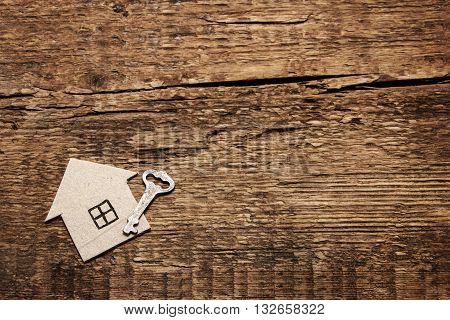 Cardboard house and key on wooden background.Wood construction