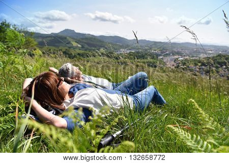 Senior couple relaxing in field on hiking day