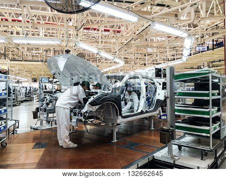 PRACHINBURI Thailand - May 12 2016: Employees of Honda Automobile Thailand work on a automobile assembly line of car body parts at Prachinburi plant in Rojana Industrial Park.