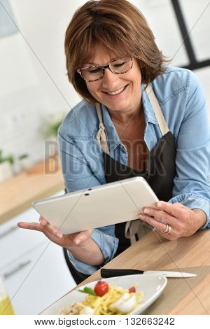 Senior woman taking pictures of dishes for blog