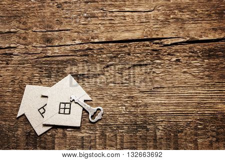 Two cardboard house and key on wooden background. Construction of wooden houses eco-friendly