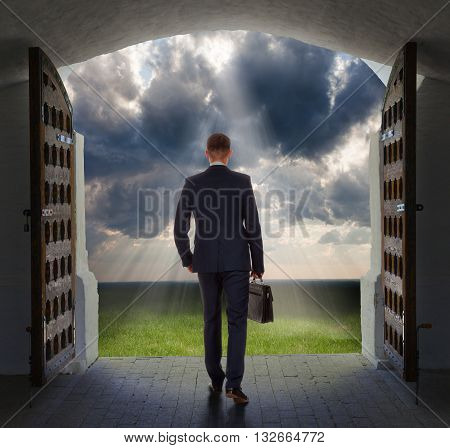 Young businessman exits from gate and moves toward the glowing heavens.