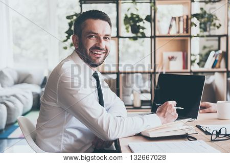 Always ready to help you. Confident mature man in shirt and tie looking at camera and smiling while sitting at his working place in office