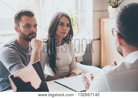Listening to financial advisor. Concentrated young couple bonding to each other and listening to some man sitting in front of them at the desk in office