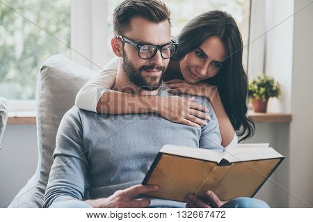 Reading their favorite book. Beautiful young woman bonding to her husband while he is reading a book on the couch
