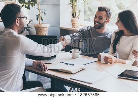 Sealing a deal. Cheerful young man bonding to his wife while shaking hand to man sitting in front of him at the desk
