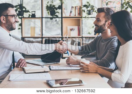 Deal! Side view of cheerful young man sitting close to his wife and shaking hand to man sitting in front of him at the desk