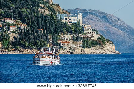 Dubrovnik Croatia - August 26 2015. Boat full of tourists seen from Old Town Harbour in Dubrovnik. View with abandoned Hotel Belvedere