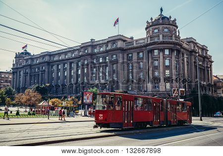 Belgrade Serbia - August 29 2015. Red tram car on the street in Belgrade. View with building of Serbian Ministry of Foreign Affairs
