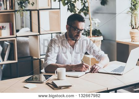 Making some notes. Concentrated mature man writing something in note pad while sitting at his working place in office