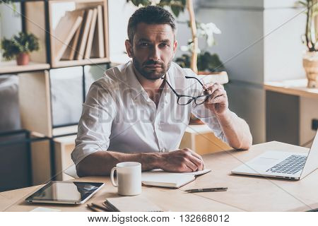 How may I help you? Confident mature man carrying his eyeglasses and looking at camera while sitting at his working place in office