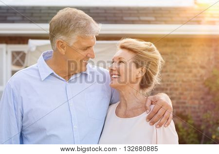 Happy senior couple standing out of the house and looking at each other. Portrait of smiling senior couple in love. Retired elderly man in love with senior wife.
