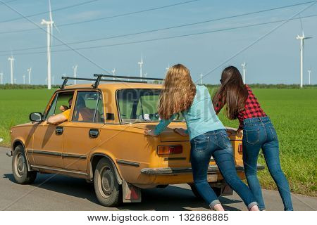 Young hipster friends on road trip on a summers day. Engine break down.Two girls pushing a vintage car while man is emboldening their.Travel adventure unforeseenteamwork funny concept