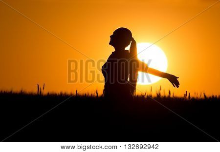 Silhouette Of Girl With Raised Hands At Sunset