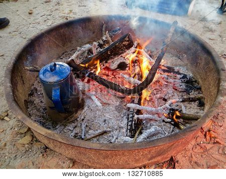 Old blue coffeepot boiling water on the campfire