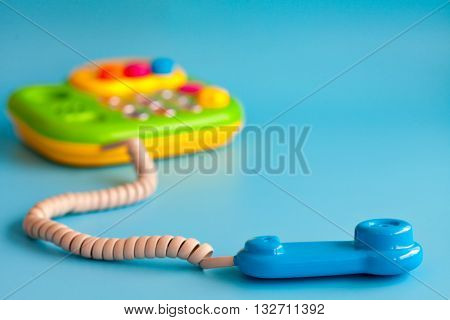 Children's toy phone with a tube of plastic on a blue background. Call on the phone. Copy space.