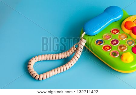 Children's toy phone with a tube of plastic on a blue background. Copy space.