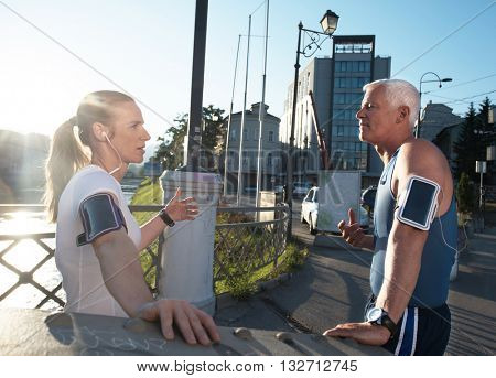 jogging couple check music playlist on phone and plan route before morning running workout  with sunrise in the city  and sun flare in background