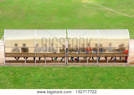 Soccer Players And Staff Sit On Bench Beside The Soccer Field