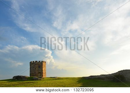 19th century sandstone customs tower at La Perouse, Sydney, Australia, with clouds in blue sky background