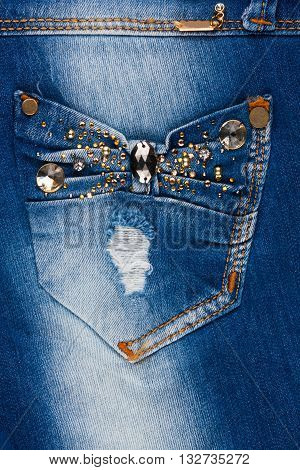 Jeans with pockets close-up decorated with rhinestones may be used as background