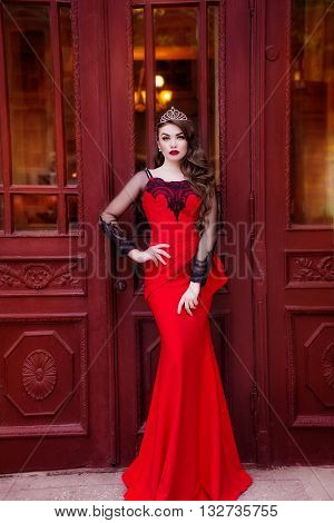 Beautiful young girl in a red evening long dress. The beauty queen in a red dress with long hair and a tiara on her head