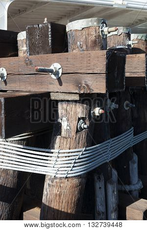 The metal hawser on the wooden post
