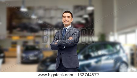 auto business, car sale and people concept - happy smiling businessman or dealer in suit over auto show background