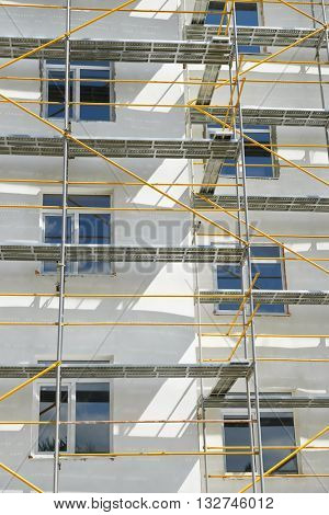 scaffolding near a house under construction for external plaster works, high apartment building in city, white wall and window, yellow pipe