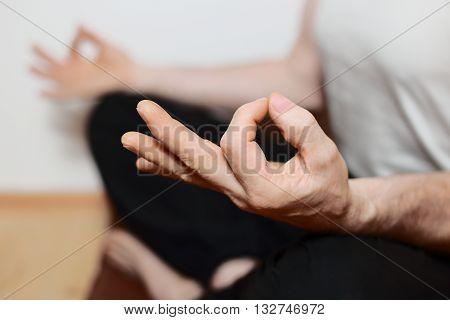sitting man is doing yoga meditation on floor