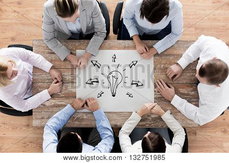 business, people, inspiration and team work concept - close up of business group sitting at table with bulb doodle on paper sheet in office