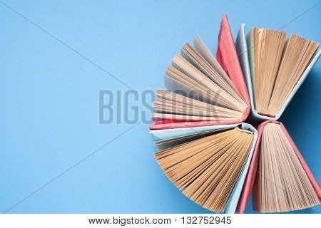 Top view of colorful hardback book in a circle. Open book fanned pages free copy space. Back to school copy space. Education background.