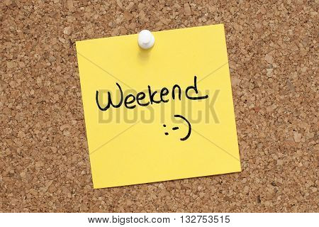 Weekend Note Concept / Yellow adhesive reminder with weekend text on corkboard
