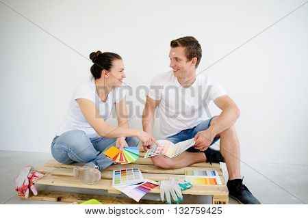 Cheerful couple chooses color of paint for repair in the room. They sit on a floor and look at each other. In their hands examples of color. Good mood.Pure white wall behind their backs