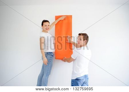The young couple is going to paste over walls with wall-paper. The guy and the girl have applied the untwisted roll of orange wall-paper to a white wall. The girl looks in a camera and laughs.